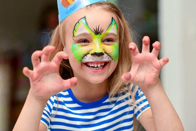 Child in makeup growls with claws hands
