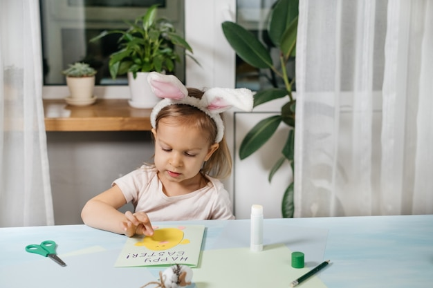 Child making easter egg gift card with a bunny from paper at home. handmade. project of children's creativity, handicrafts, crafts for kid, toddler.