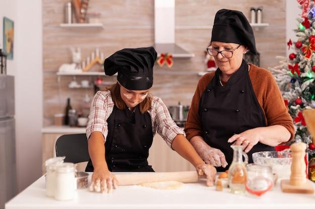 クリスマス休暇を祝う祖母とジンジャーブレッド自家製デザートを作る子供