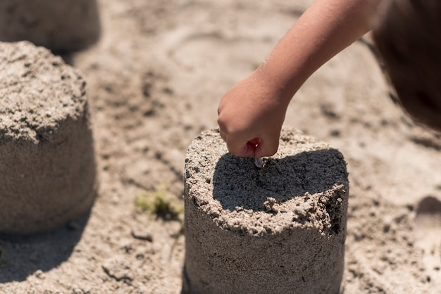 Child making sandcastle at the beach