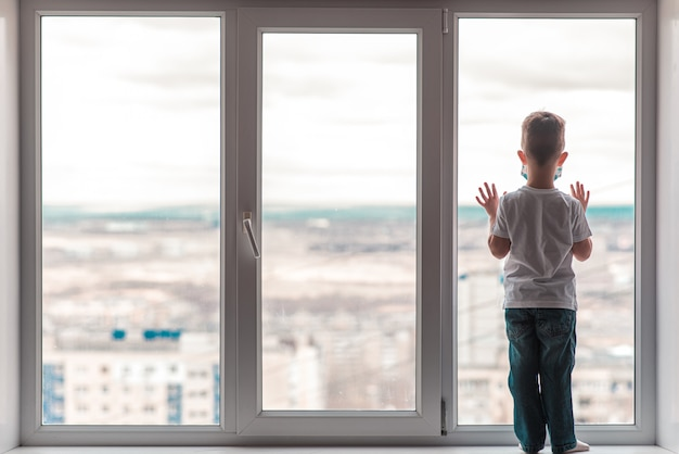 A child in a medical mask is sitting at home in quarantine because of coronavirus and covid -19 and looks out the window.