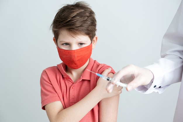 A child in a medical mask is vaccinated against the coronavirus in the covid pandemic