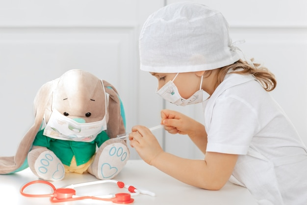 Child in medical mask playing doctor and makes injection of vaccine to toy. kid play role game at home.