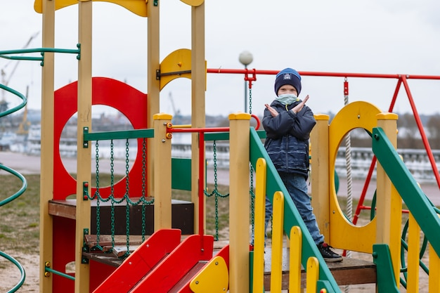 A child in a medical mask showing a stop gesture on the playground