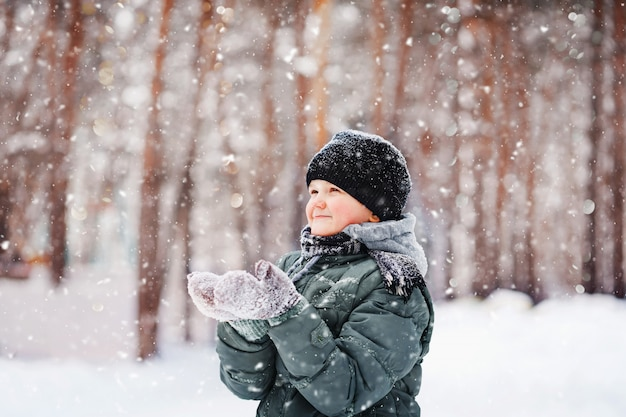 Child in mittens stretches her hand to catch falling snowflakes.. first snow, winter, health, childhood concept.