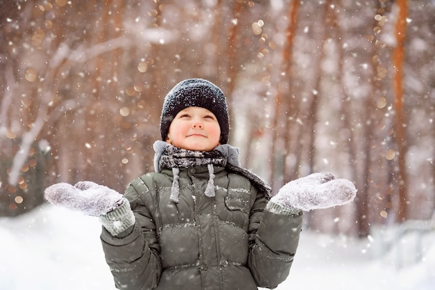 Child in mittens stretches her hand to catch falling snowflakes.