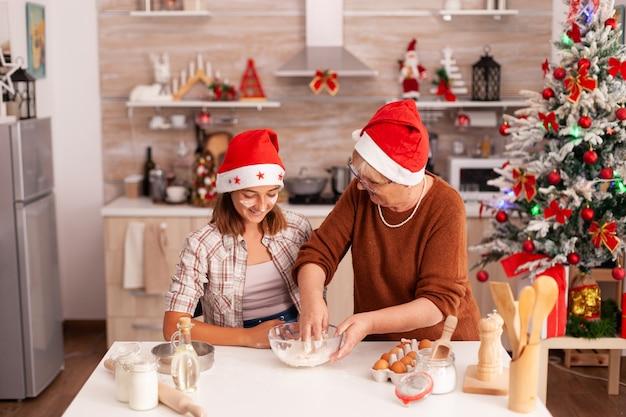Bambino che mescola gli ingredienti dei biscotti in una ciotola per fare un impasto tradizionale fatto in casa