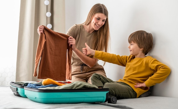 Child and mother at home preparing luggage for traveling