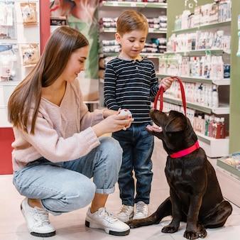 Bambino e madre al negozio di animali con il loro cane