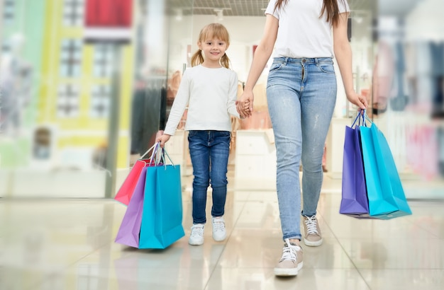 Child and mother with colorful shopping bags in store.