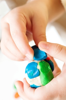 Child moulds from modeling clay on table, baby hands with plasticine