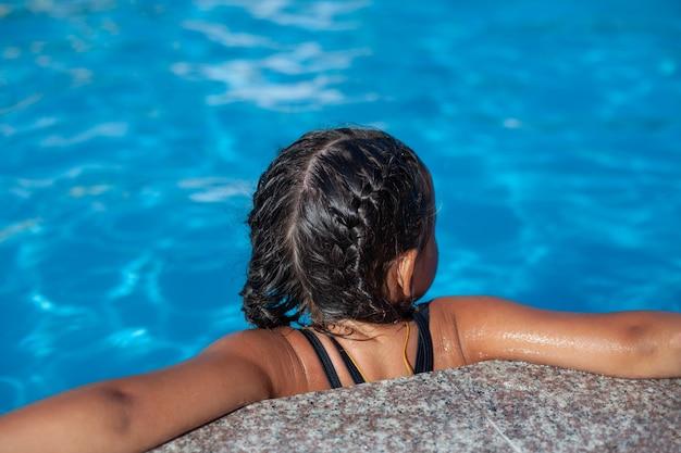 プールの近くの子供は、頭に編みこみのピグテールを付けた日焼けした小さな女の子が、花崗岩の側に手を置いています...