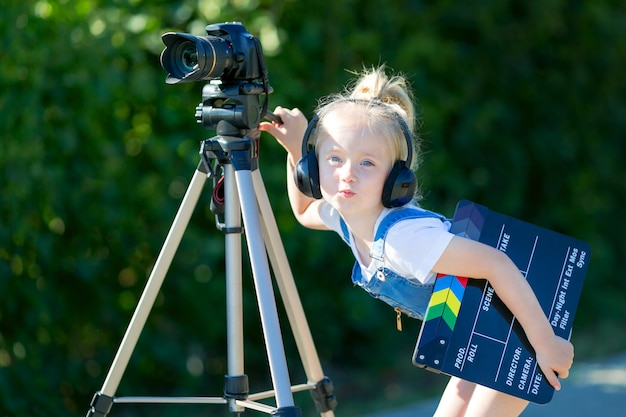Child novice video blogger with a camera and a tripod.