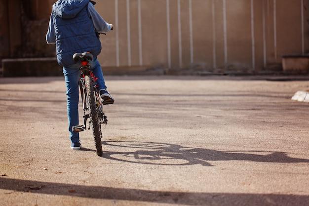 晴れた春の日にアスファルトの道路で自転車に乗る子。背面図