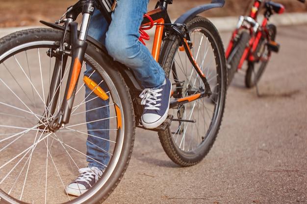 晴れた春の日にアスファルトの道路で自転車に乗る子。ペダルと足のクローズアップ