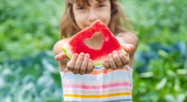 Ребенок на пикнике ест арбуз.