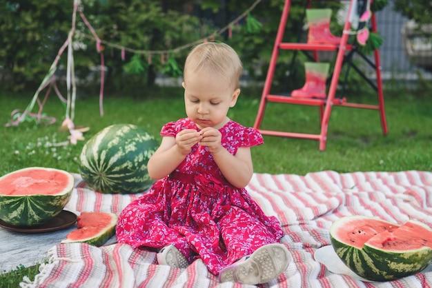 Ребенок на пикнике в парке ест большие арбузы. летняя семейная вечеринка на открытом воздухе с малышкой