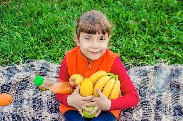 주스와 과일 피크닉에 아이입니다. 선택적 초점.