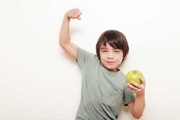 Ребенок на белом фоне ест зеленое яблоко, которое он держит в одной руке, а другой показывает нам свой бицепс, показывая силу