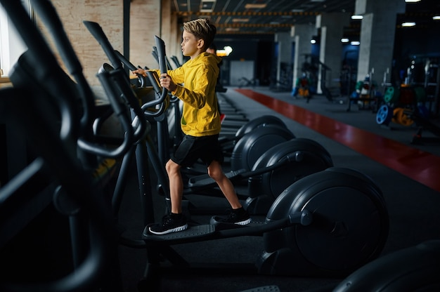 운동 기계, 측면보기, 체육관에서 훈련에 아이. 스포츠 클럽의 젊은이, 건강 관리 및 건강한 라이프 스타일, 운동 모범생, 낚시를 좋아하는 청소년