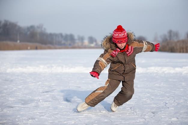 冬の氷の上の子供。その少年は氷の湖でスケートをしている。