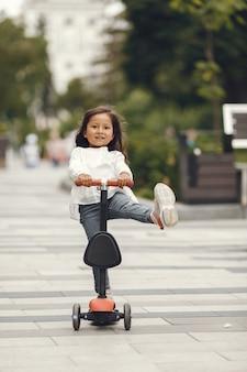 Ребенок на самокате в парке. дети учатся кататься на роликах. маленькая девочка на коньках в солнечный летний день.
