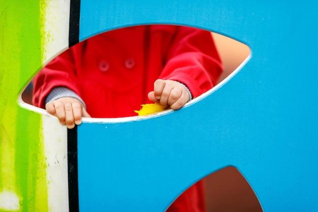 遊び場の子供。子供は盾の後ろに隠れて、穴を通して手を見せます。赤いコートを着たかなり青い目の1歳。魅力的な子供がクローズアップで手を渡します。健康な子供と子育ての概念