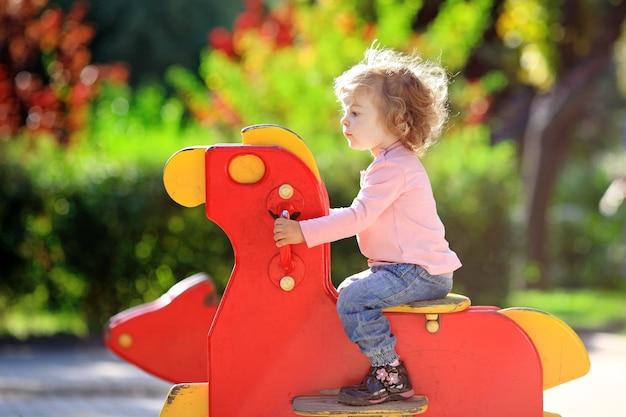 Ребенок на детской площадке в летнем парке