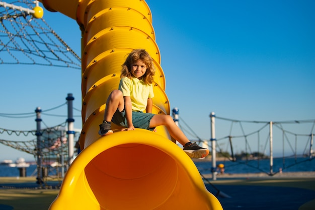 슬라이드 놀이터 지역에 아이입니다. 재미있는 귀여운 꼬마가 놀이터의 터널 미끄럼틀에 앉아 있습니다.