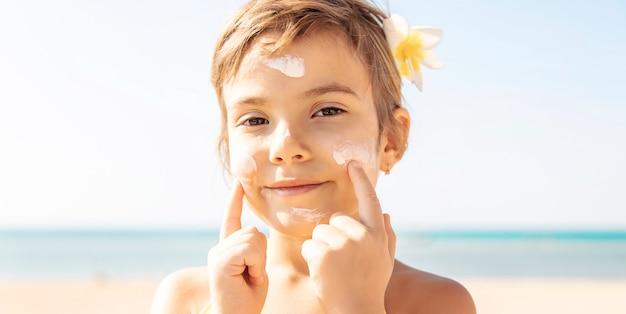 ビーチの子供が日焼け止めを塗る