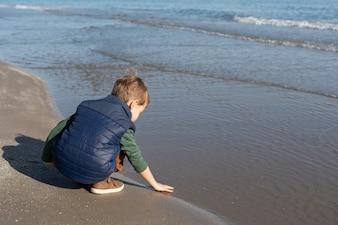 Ребенок на берегу пляжа играет с волнами