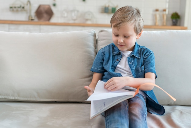 Ребенок на диване смотрит в тетрадь