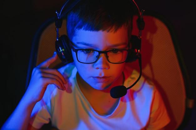 어린이 온라인 방송 컴퓨터 게임, 소년은 rgb 조명 배경에서 헤드폰으로 스트리밍