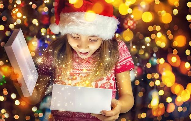 Ребенок открывает подарки под елкой. выборочный фокус. праздничный день.