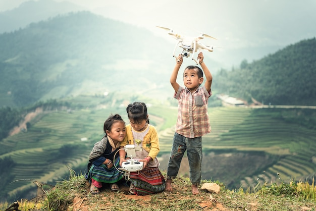 Child operating drone flying or hovering by remote control in countryside of vietnam
