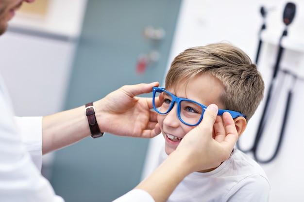Child optometry male optometrist optician doctor examines eyesight of little boy