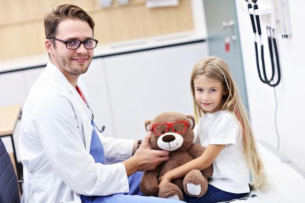 子供の検眼男性検眼医の眼鏡技師は、少女の視力を調べます