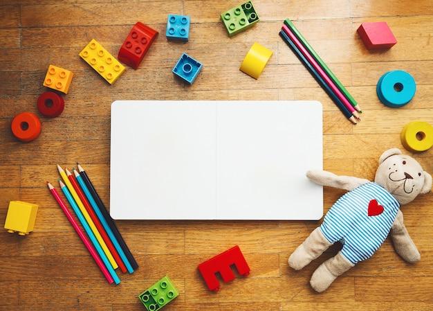 空の本やメモ帳、おもちゃの木製ブロック、プラスチックコンストラクター、色鉛筆、テディベアがセットになった子供または赤ちゃんの遊び。学校に戻る、教育の概念。幼稚園または就学前の背景。