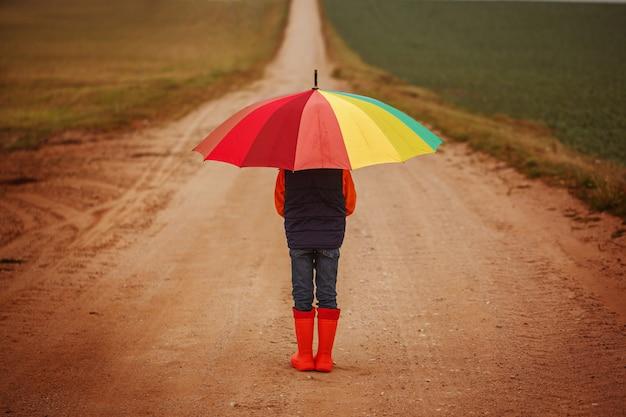 Child in orange rubber boots holding colorful umbrella under rain in autumn. back view