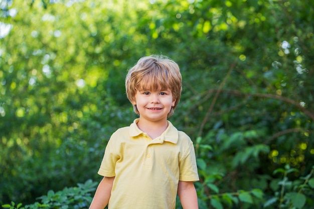 Child outdoors in nature. happy child. funny baby boy isolated on a background of green trees. smiling child boy. cheerful cheerful kid.