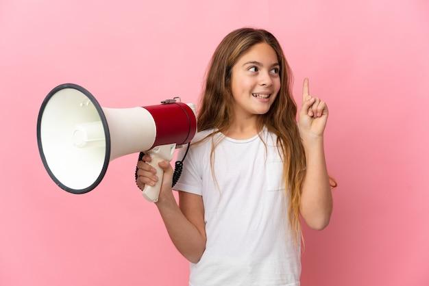 Ребенок на изолированном розовом фоне держит мегафон и намеревается реализовать решение