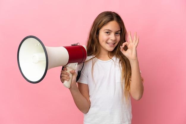 Ребенок на изолированном розовом фоне держит мегафон и показывает пальцами знак ок