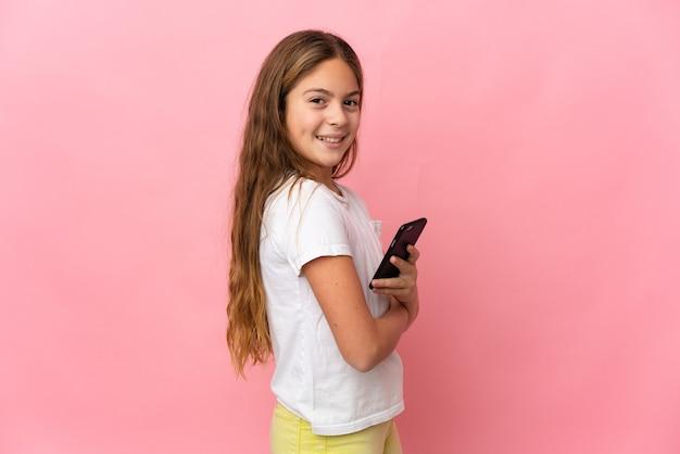 Ребенок на изолированном розовом фоне держит мобильный телефон со скрещенными руками