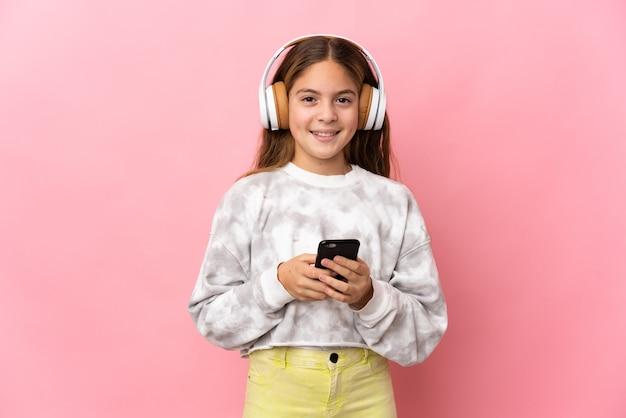 Ребенок на изолированном розовом фоне, слушает музыку с мобильным телефоном и смотрит вперед