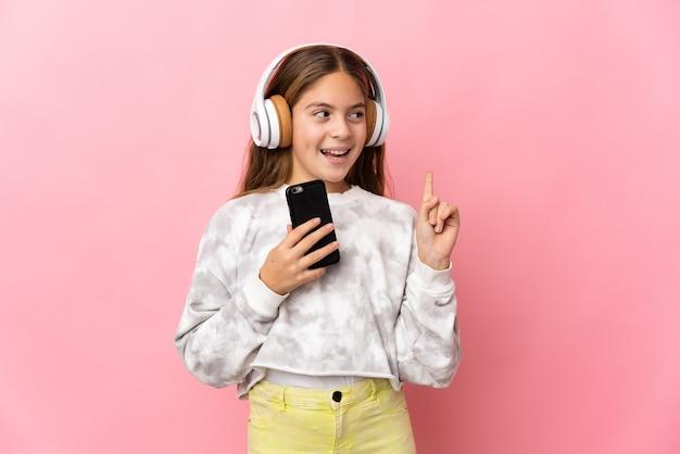 Ребенок на изолированном розовом фоне, слушает музыку с помощью мобильного телефона и поет