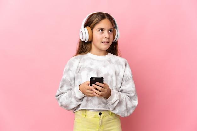Ребенок на изолированном розовом фоне, слушает музыку с помощью мобильного телефона и думает