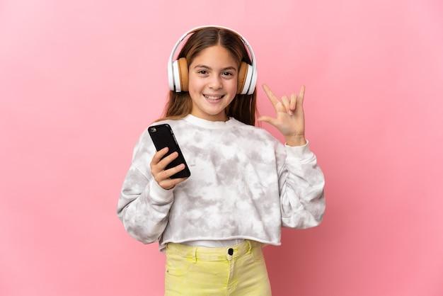 孤立したピンクの背景の上の子供がロックジェスチャーを作るモバイルで音楽を聴いています