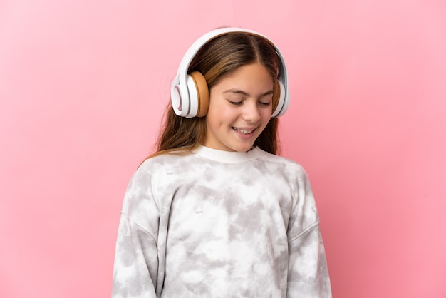 Ребенок на изолированном розовом фоне прослушивания музыки