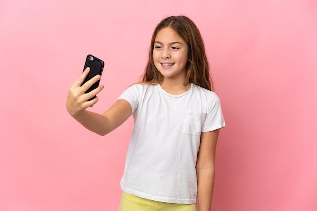 Ребенок на изолированном розовом фоне, делая селфи с мобильным телефоном