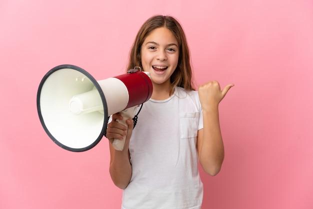 Ребенок на изолированном розовом фоне кричит в мегафон и указывает сторону